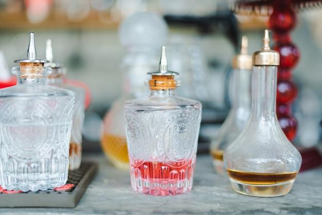 Butelki szklane, karafki ze szkła ciętego w stylu vintage i kryształowe karafki z różnymi napojami alkoholowymi i likierami