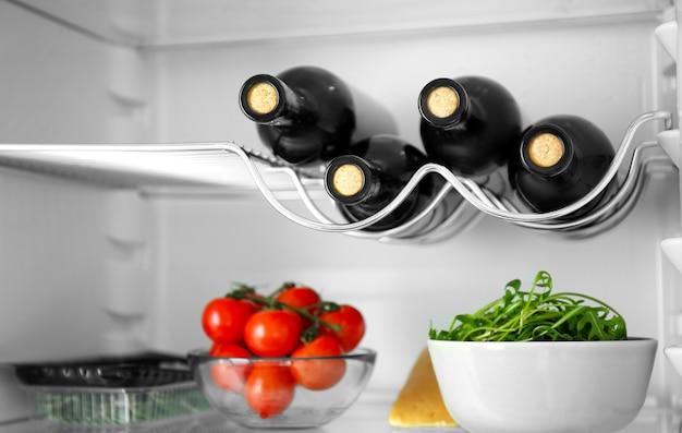Butelki wina i produkty w lodówce