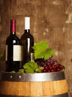 Butelki wina na dębowej beczce na starym odrapanym drewnianym tle