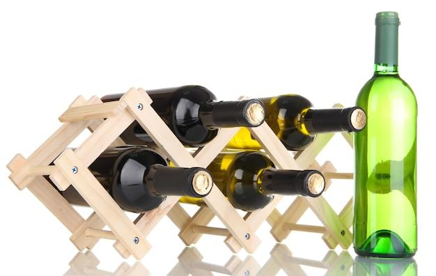 Butelki wina umieszczone na drewnianym stojaku na białym tle