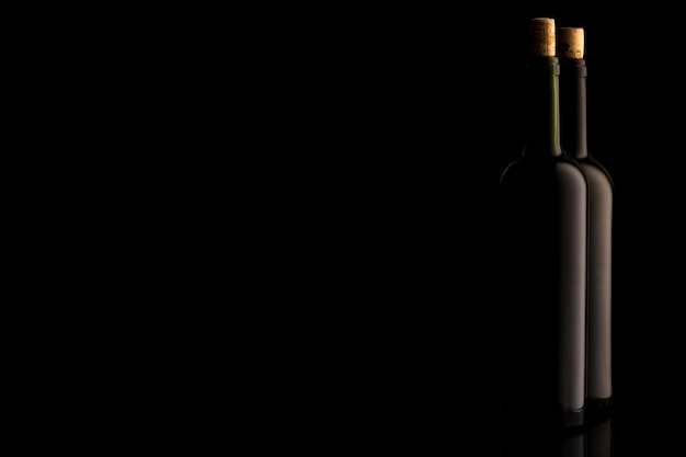 Butelki wina z korkiem i na czarnym tle na białym tle