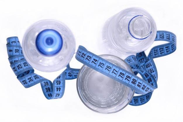 Butelki wody, szklanka wody i taśma miernicza na białym tle