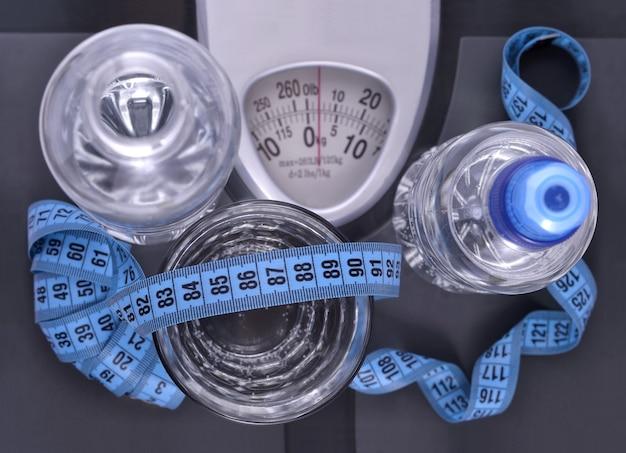 Butelki wody, szklanka wody i taśma miernicza na wadze