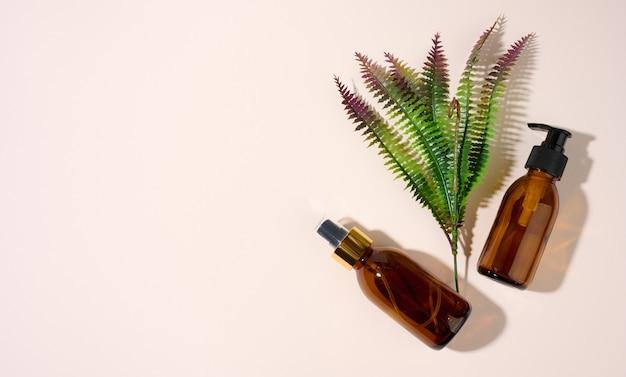 Butelki z brązowego szkła z dozownikiem i gałązką paproci na beżowym tle. opakowania na żel, serum, reklama i promocja. naturalne produkty ekologiczne. makieta