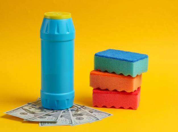 Butelki z detergentem, gąbki do czyszczenia z banknotami stu dolarowymi na białym tle