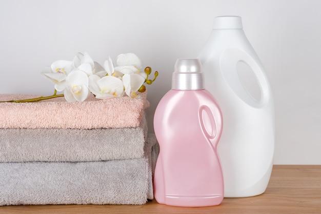 Butelki z detergentem i płynem do zmiękczania tkanin z czystymi ręcznikami i kwiatami orchidei na drewnianym stole. pojemniki na środki czystości. płynny detergent i odżywka. pralnia, koncepcja czyszczenia.