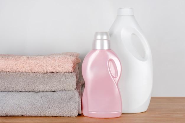 Butelki z detergentem i płynem do zmiękczania tkanin z czystymi ręcznikami na drewnianym stole. pojemniki na środki czystości. płynny detergent i odżywka. pralnia, koncepcja czyszczenia.