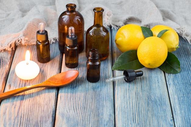 Butelki z dozownikiem oleju, drewniana łyżka, świeca i cytryny