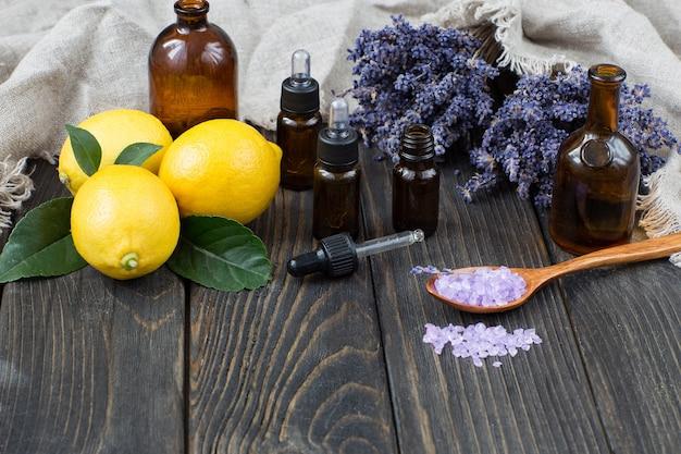 Butelki z dozownikiem oleju, drewniana łyżka z solą, kwiaty lawendy i cytryny