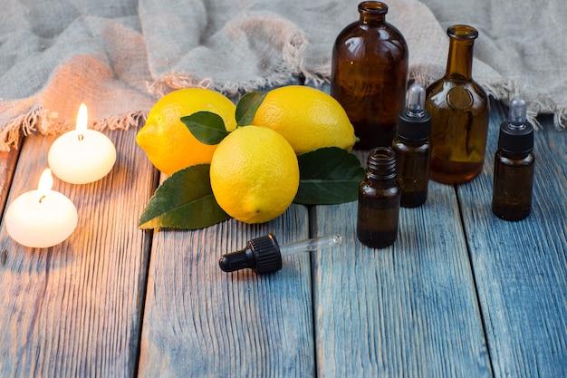 Butelki z dozownikiem, oliwą, świecami i cytrynami