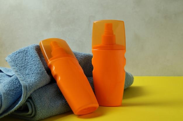 Butelki z filtrem przeciwsłonecznym i ręczniki na żółtym stole
