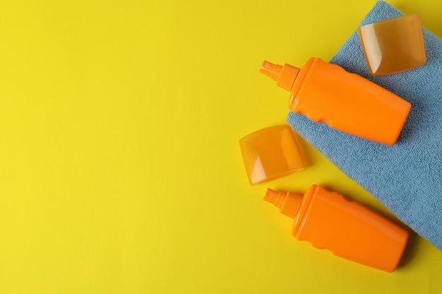 Butelki z filtrem przeciwsłonecznym i ręczniki na żółtym tle na białym tle