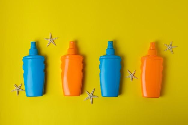 Butelki z filtrem przeciwsłonecznym i rozgwiazdy na żółto