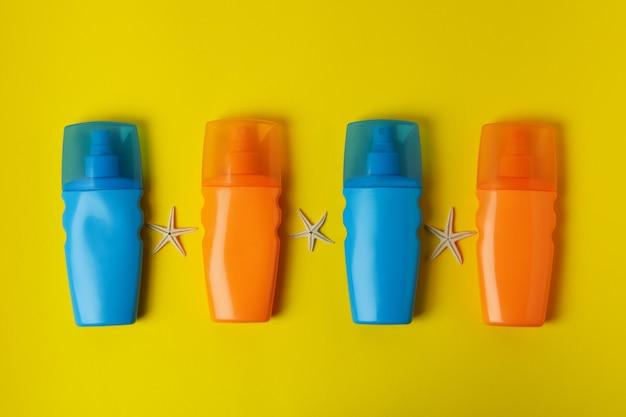 Butelki z filtrem przeciwsłonecznym i rozgwiazdy na żółtym tle na białym tle