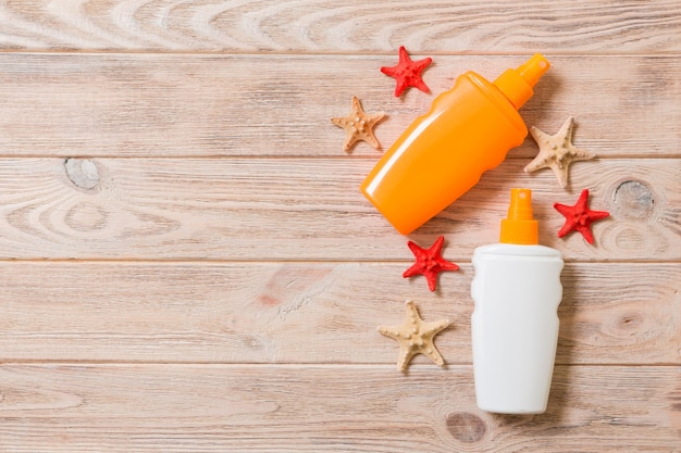 Butelki z filtrem przeciwsłonecznym z muszelek i rozgwiazdy na drewnianym stole z miejsca na kopię. mieszkanie świeckich koncepcja letnich wakacji.