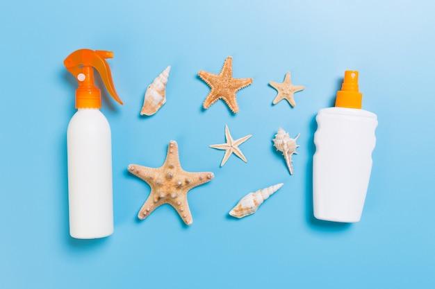 Butelki z filtrem przeciwsłonecznym z muszelkami na niebieskim widoku z blatu