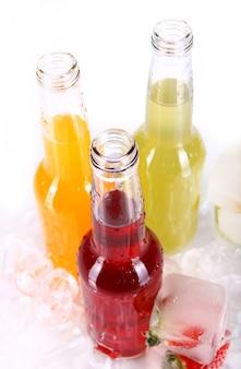 Butelki z kolorowym koktajlem i lodem