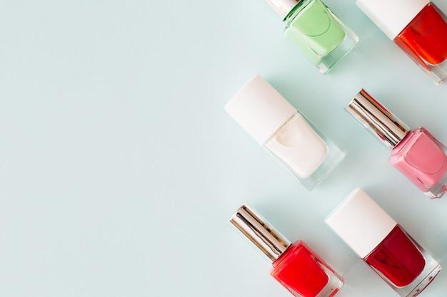 Butelki z kolorowym lakierem do paznokci na pastelowym niebieskim tle koncepcja manicure i pedicure z płaskim blatem