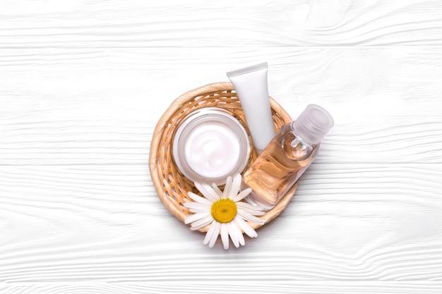 Butelki z kosmetykami i kwiatami rumianku w wiklinowym koszu. krem, tonik, peeling wodny i do twarzy. białe rurki. makiety naturalnych produktów kosmetycznych.