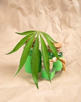 Butelki z olejem ekstraktu i marihuaną medyczną na tle papieru.