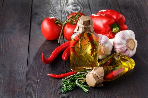 Butelki z olejem, ziołami i przyprawami na stole drewna na czarno