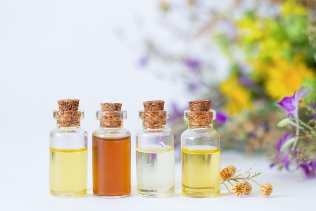 Butelki z organicznymi olejkami eterycznymi na tle kwiatów polnych i suszonych ziół
