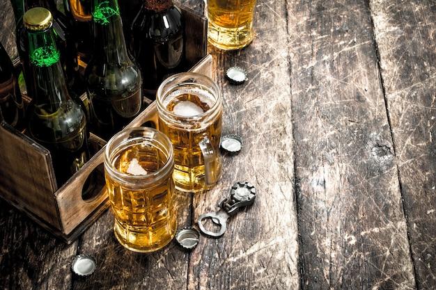 Butelki z piwem w starym pudełku na drewnianym stole.