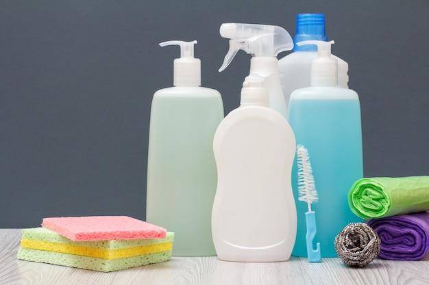 Butelki z płynem do mycia naczyń, płynem do mycia szyb i płytek, detergentem do kuchenek mikrofalowych i kuchenek, ścierki, szczotka, gąbka metalowa i worki na śmieci na szarym tle. koncepcja mycia i czyszczenia.