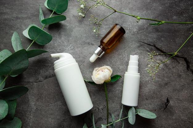Butelki z serum i słoiczki kremów kosmetycznych na szarym tle z gałązkami eukaliptusa i zielenią
