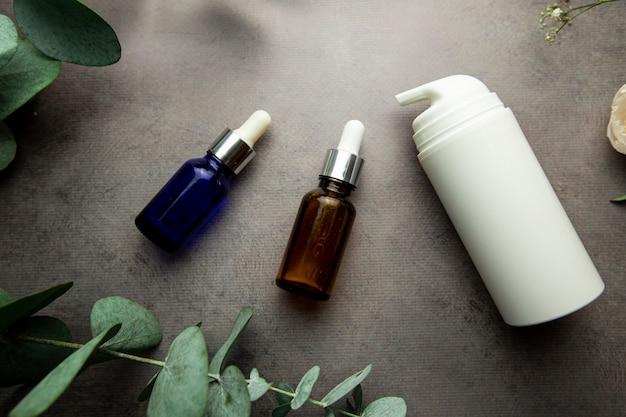 Butelki z serum i słoiczki kremów kosmetycznych na szarym tle z gałązkami eukaliptusa