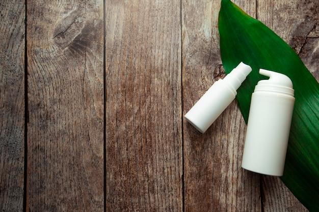 Butelki z serum i słoiki kremów kosmetycznych na szarym tle z gałązkami eukaliptusa i zielonymi liśćmi produkty kosmetyczne na drewnianym tle