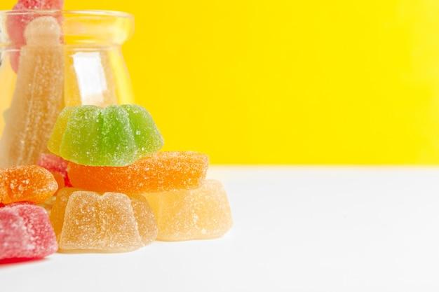 Butelki z słodkimi cukierkami na stołowym tle