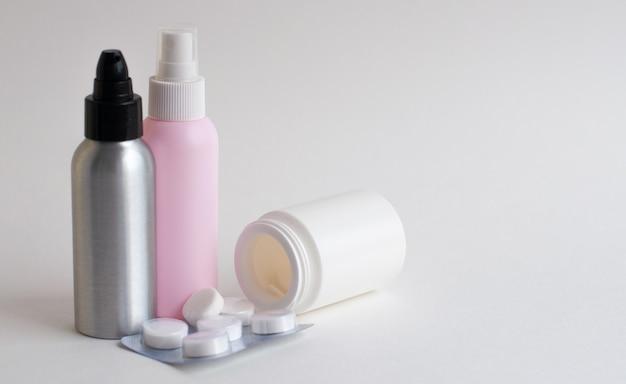 Butelki z tabletkami w kolorze białym, różowym, szarym na szarym tle. skopiuj miejsce