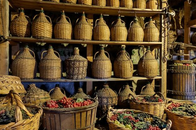 Butelki z winem i kosze z winogronami w starej winiarni