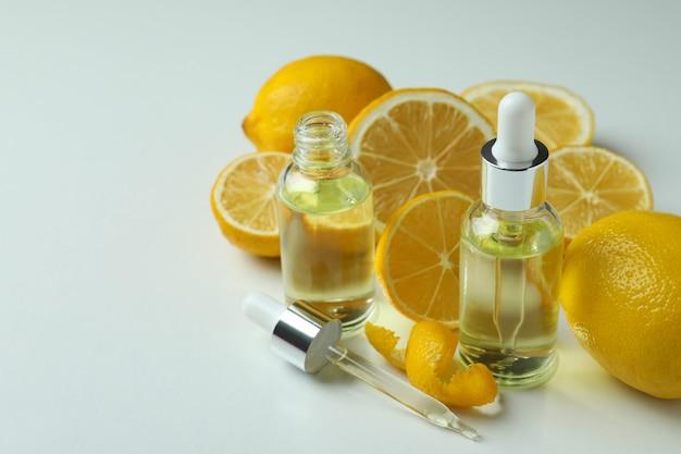 Butelki z zakraplaczem z olejem i cytrynami na białym stole