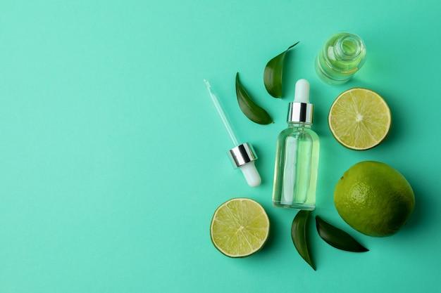 Butelki z zakraplaczem z olejem i limonki na tle mięty na białym tle