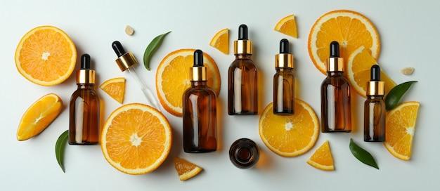 Butelki z zakraplaczem z olejem i plastrami pomarańczy na białym stole