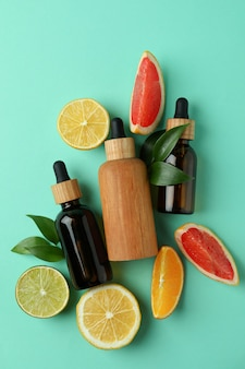 Butelki z zakraplaczem z olejkiem i cytrusami na miętowym tle