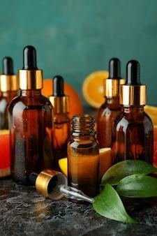 Butelki z zakraplaczem z oliwą i różnymi cytrusami na czarnym dymnym stole