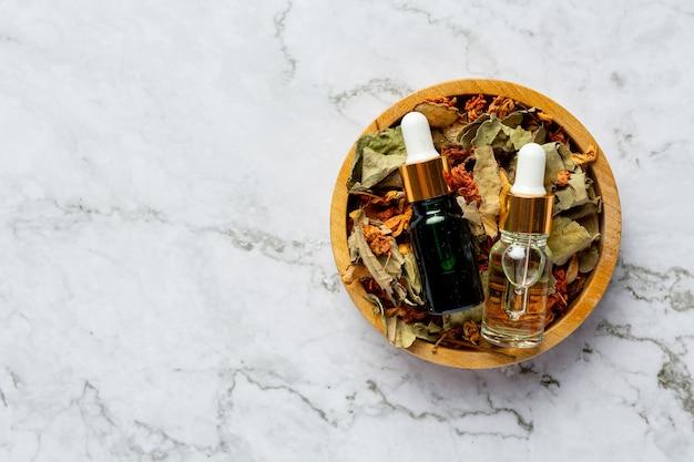 Butelki z ziołowym olejem leczniczym umieszczonym w drewnianej misce