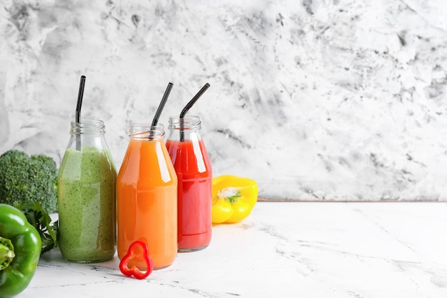 Butelki zdrowego smoothie z różnymi warzywami na jasnej powierzchni