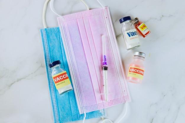 Butelki ze szczepionką sars-cov-2 zawierające szczepionki covid-19 w strzykawce medycznej i ochronnej masce chirurgicznej