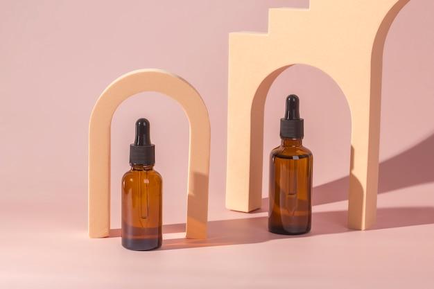 Butelki ze szkła bursztynowego z modnymi geometrycznymi kształtami łuków na pastelowym tle