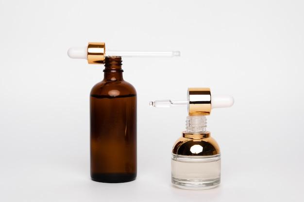 Butelki ze szkła bursztynowego z pipetą na białym tle