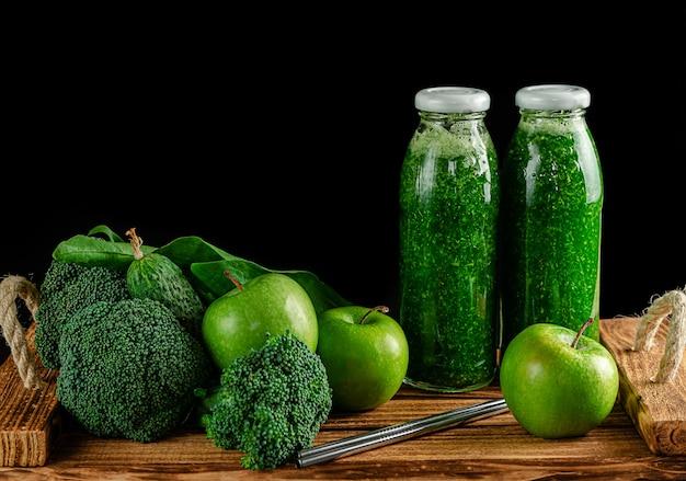 Butelki zielonego smoothie ze składnikami na czarnej ścianie.