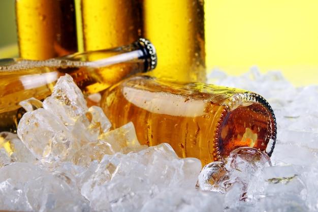 Butelki zimnego i świeżego piwa z lodem