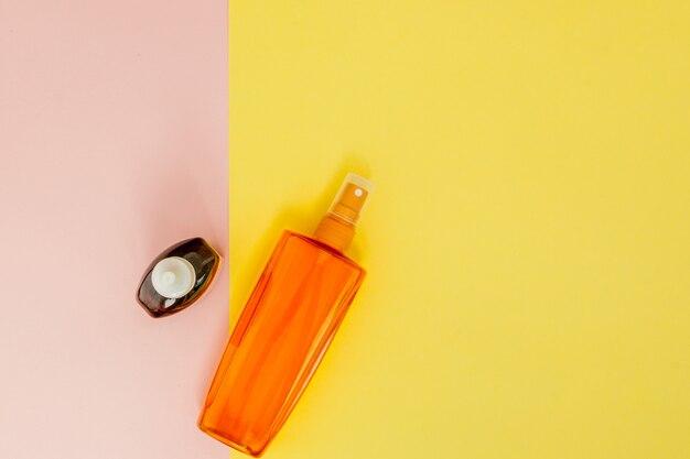 Butelkowy krem z filtrem na jasnej kwadratowej żółto-różowej przestrzeni