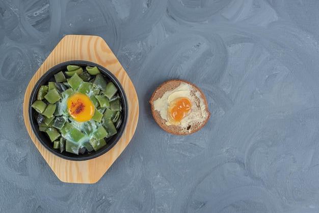 Butterbrot obok małego talerza posiekanej fasoli z polewą jajeczną na marmurowym tle.