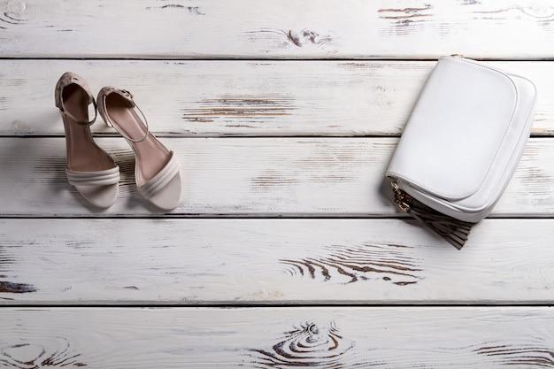 Buty damskie i mała torebka. prezentacja z obuwiem i torebką. skórzana torebka i buty na obcasie. eleganckie obuwie i skórzany dodatek.