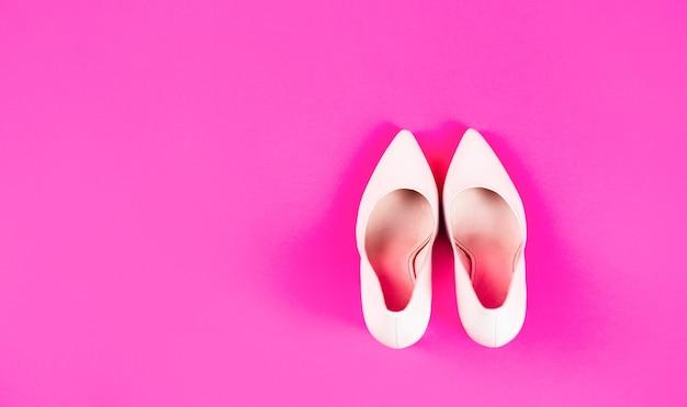 Buty damskie na wysokim obcasie na różowym tle. buty damskie. pojęcie piękna i mody. modne kobiety buty na białym tle na czerwonym tle. stylowe klasyczne damskie skórzane buty.